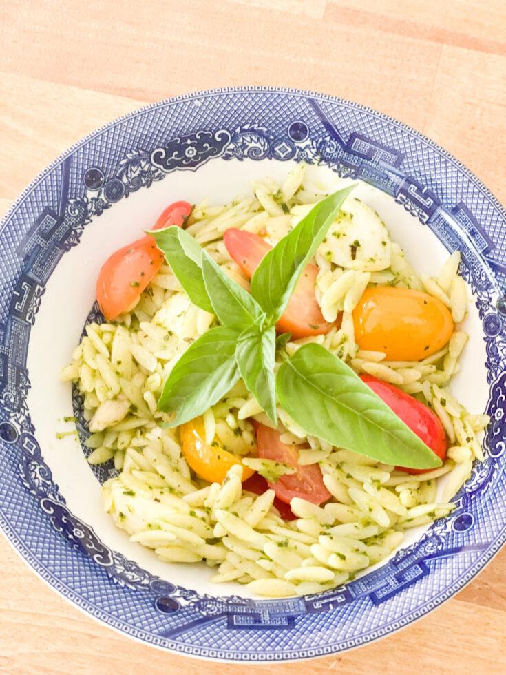 orzo pesto pasta, fresh tomatoes basil garnish blue and white bowl wood counter background